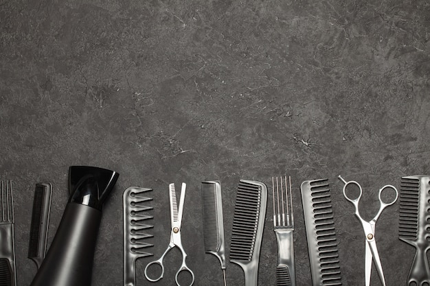 Czarne grzebienie i grzebienie z nożyczkami na czarnym tle. skopiuj miejsce na tekst.