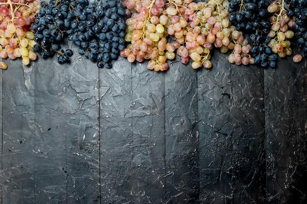 Czarne i białe winogrona. na czarnym tle rustykalnym.
