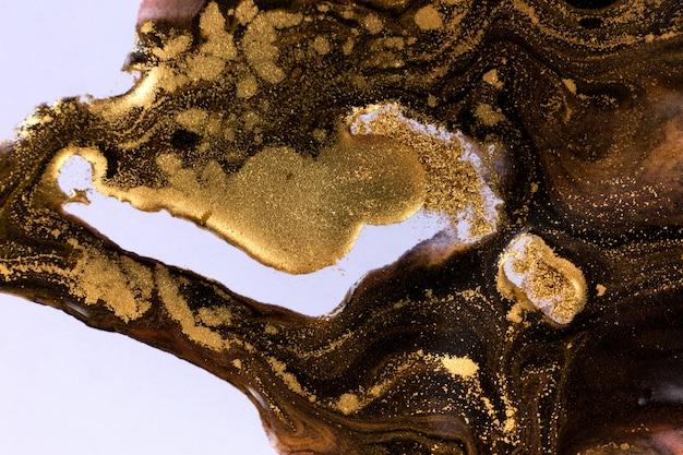 Czarne i złote mieszane atramenty rozpryskiwane na tle białego papieru.