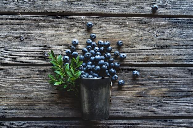 Czarne jagody w filiżance na drewnianym tle. koncepcja lato i zdrowej żywności. zdrowa żywność, zdrowie