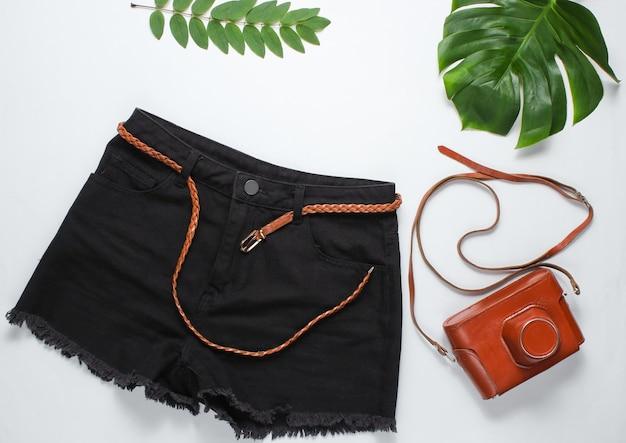 Czarne jeansowe szorty ze skórzanym paskiem, retro aparat w pokrowcu na białym tle z zielonymi tropikalnymi liśćmi.