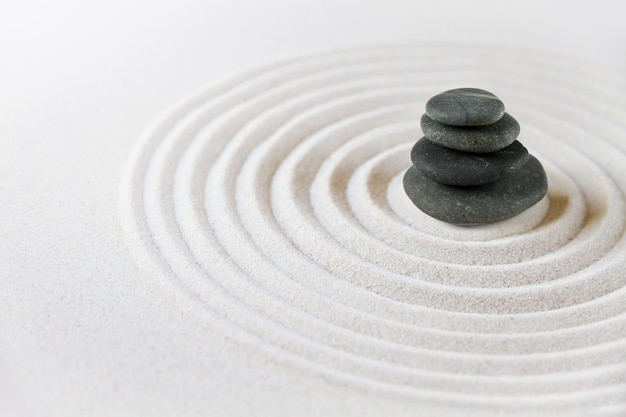 Czarne kamienie piętrzą się w piasku. powierzchnia ogrodu japońskiego zen