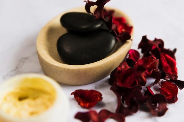 Czarne kamienie zen w marmurowym pojemniku z suchymi czerwonymi płatkami orchidei