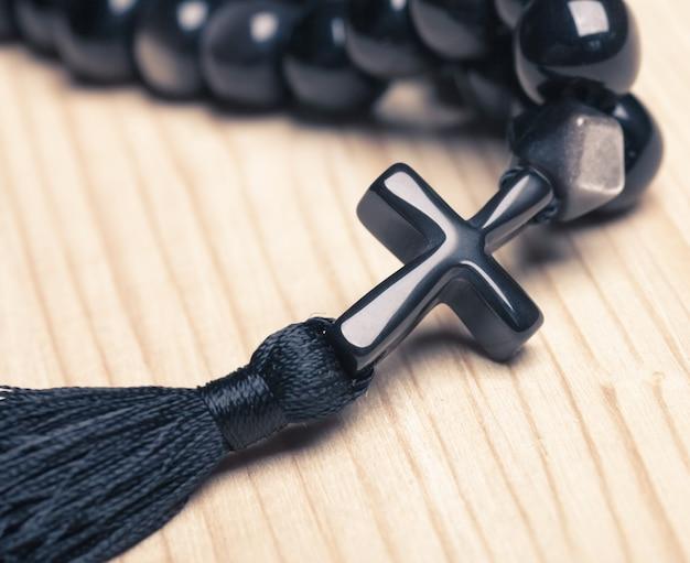 Czarne kamienne koraliki chrześcijańskie z krzyżem na drewnianym biurku
