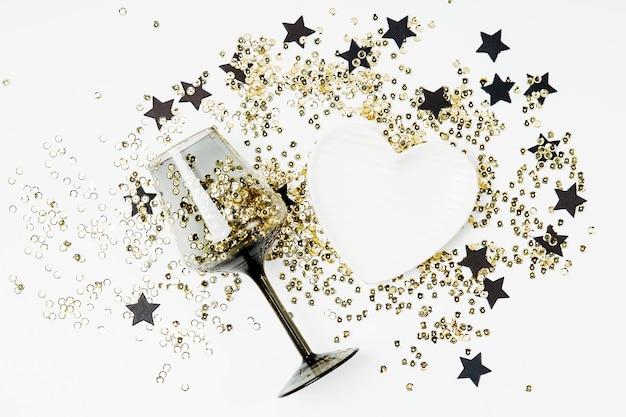 Czarne kieliszki do wina ze złotym konfetti i czarnymi gwiazdami na białym tle. płaski świeckich, widok z góry. koncepcja święta i uroczystości.