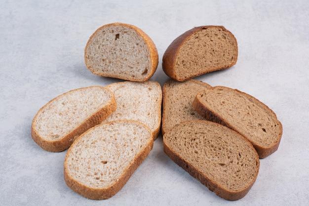 Czarne kromki chleba żytniego na kamiennej powierzchni