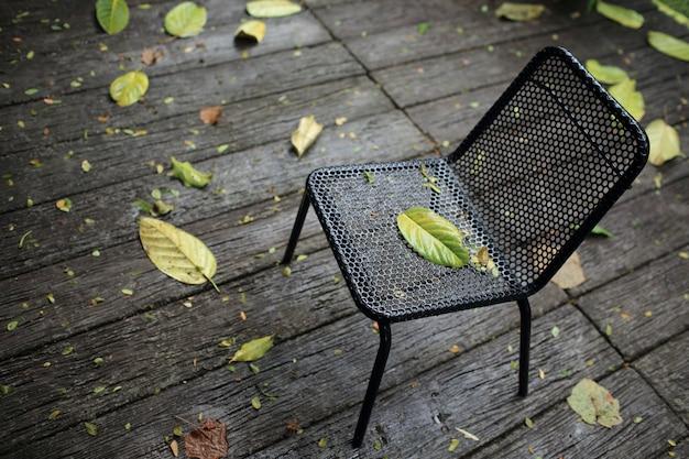 Czarne krzesło po opadach deszczu w ogrodzie.