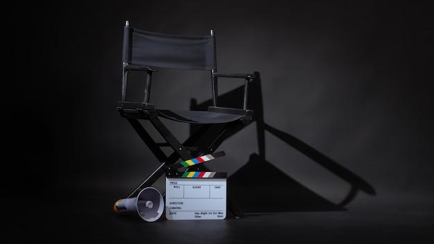 Czarne krzesło reżysera biała tablica clapper lub tabliczka filmowa na podłodze z megafonem na czarnym tle