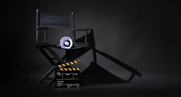 Czarne krzesło reżysera i deska clapper lub film clapperboard z megafonem na czarnym tle. zastosowanie w produkcji wideo lub przemyśle kinowym