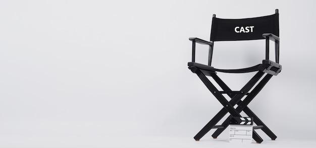 Czarne krzesło reżysera i mały biały łupek lub tablica klapy lub łupek filmowy do wykorzystania w produkcji wideo...