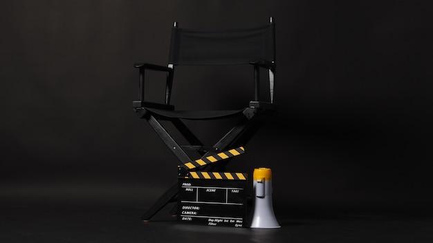 Czarne krzesło reżysera i tablica clapper lub tablica filmowa clapperboard z żółtym megafonem na czarnym tle. użyj w produkcji wideo lub w przemyśle filmowym