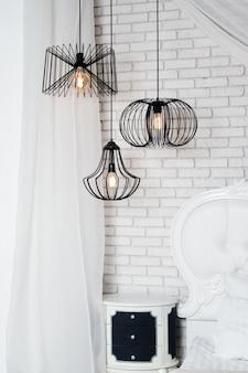 Czarne lampy w jasnym wnętrzu sypialni. wiszące trzy nowoczesne czarne lampy