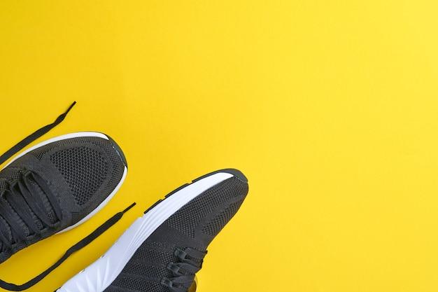 Czarne męskie trampki na żółtym tle. koncepcja bloga lub magazynu mody. męskie buty, modne trampki, moda, styl życia. makieta. płaski widok z góry kopia przestrzeń minimalne tło.