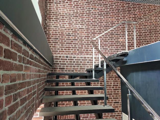 Czarne metalowe schody balustradowe i dekoracja wnętrz ceglanych ścian