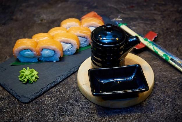 Czarne naczynia do sosu sojowego na drewnianej desce okrągłej na tle rolek sushi na płycie kamiennej