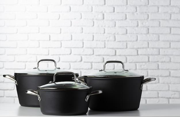 Czarne naczynia kuchenne na stole przed białym murem