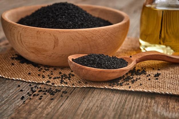 Czarne nasiona kminku w drewnianą łyżką
