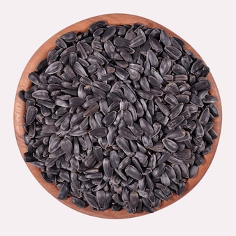 Czarne nasiona słonecznika w drewnianej misce na białym tle