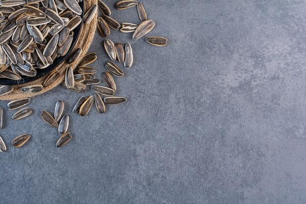 Czarne nasiona słonecznika w misce na trójnogu, na tle marmuru.