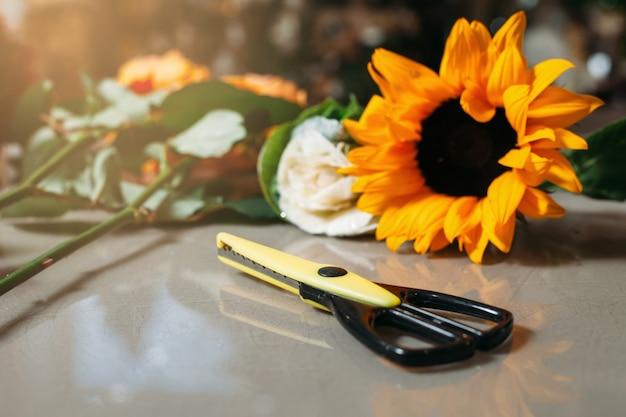 Czarne nożyczki na szarym stole przed słonecznikiem