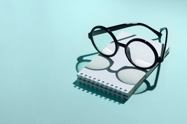Czarne okrągłe okulary leżą na notatniku i rzucają cień