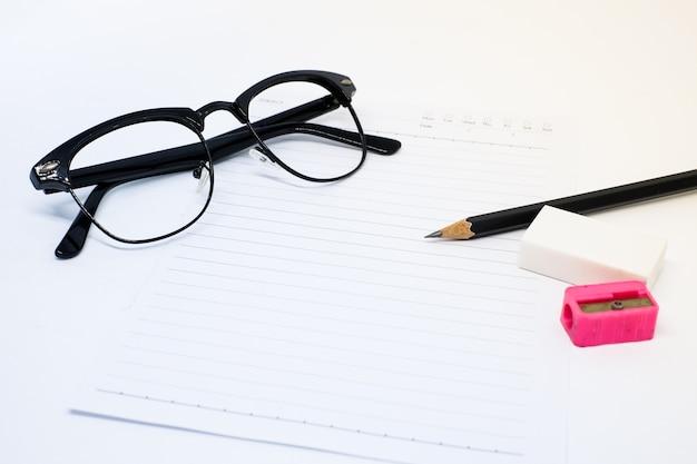 Czarne okulary, biała kartka, ołówek, różowa temperówka i gumka do pisania notatek