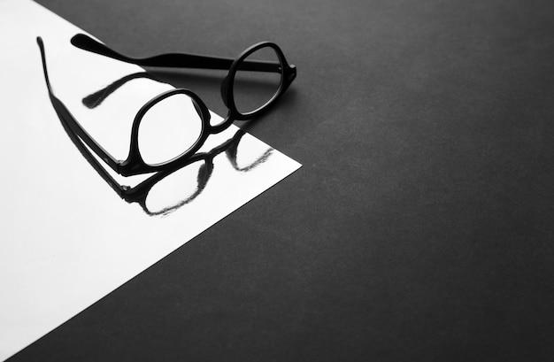 Czarne okulary mody na powierzchni odblaskowej