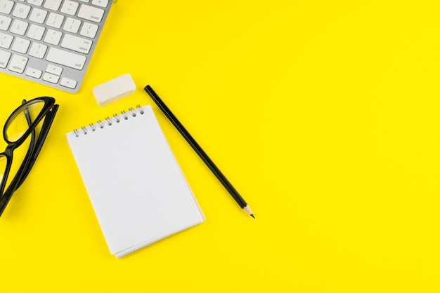 Czarne okulary, ołówek, laptop, terminarz notatnika i gumka do ścierania na żółtym tle.