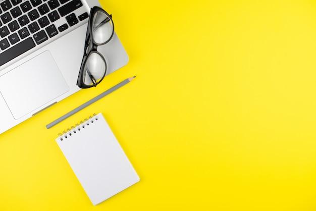 Czarne okulary, ołówek, laptop, terminarz notatnika na żółtym tle.