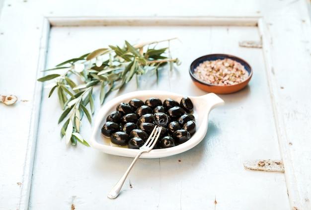 Czarne oliwki w białej płytce ceramicznej, gałęziach i przyprawach