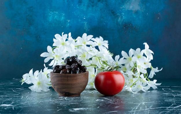 Czarne oliwki w drewnianej filiżance z pomidorem na bok.