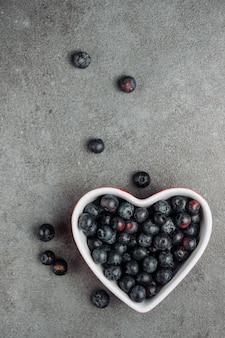 Czarne oliwki w misce w kształcie serca na szarym tle. widok z góry.