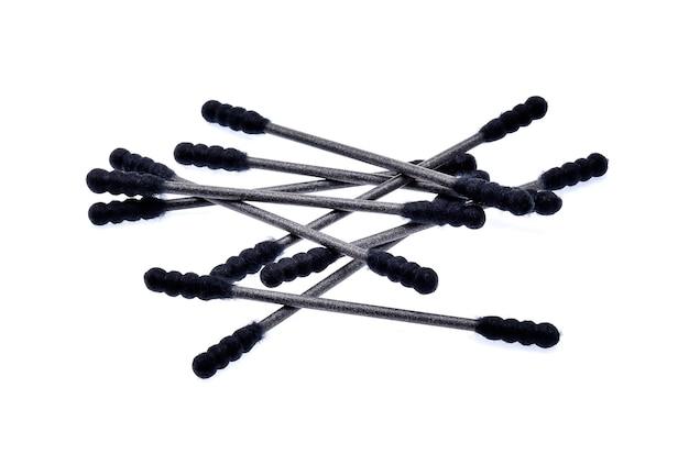 Czarne patyczki bawełniane (pączki waty) na białym tle