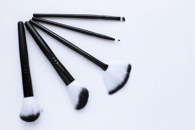 Czarne pędzle z biało-czarnym włosiem do makijażu w różnych rozmiarach leżą na białym tle...