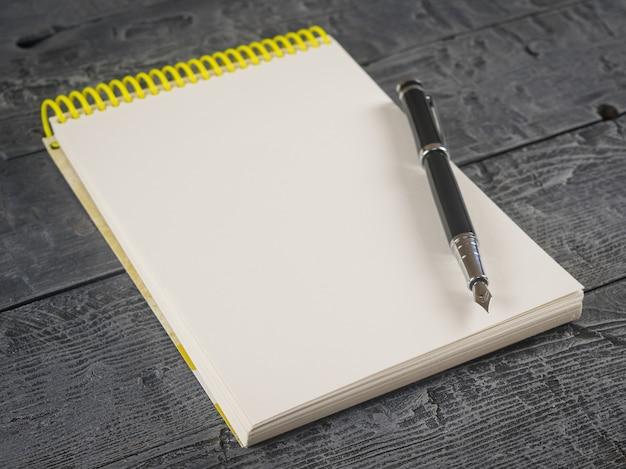 Czarne pióro wieczne z notatnikiem na ciemnym drewnianym stole. widok z góry.