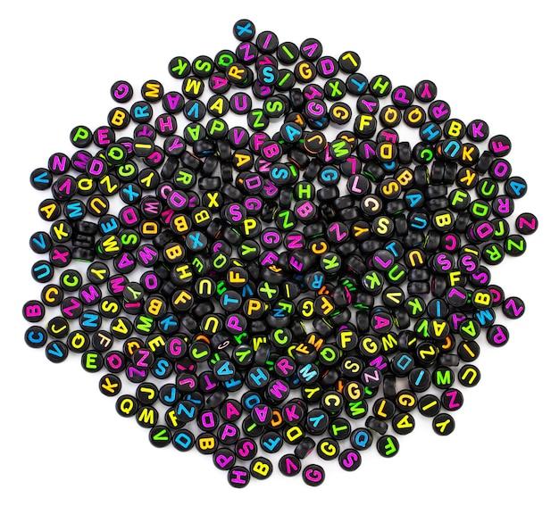 Czarne plastikowe koraliki z kolorowymi literami rozmieszczonymi losowo.