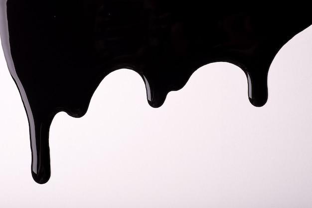 Czarne, płynne krople farby spływają na białym tle. streszczenie tło wzór kroplówki płynu.
