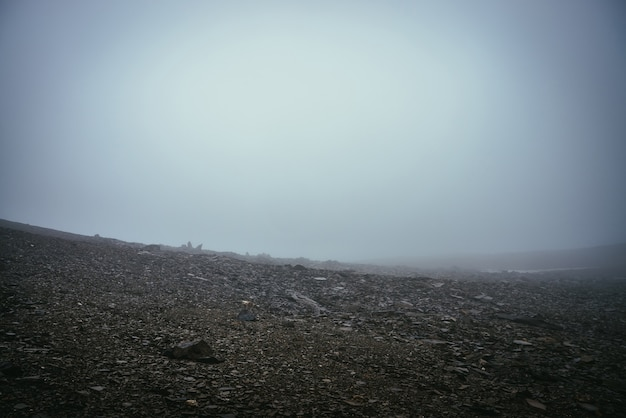 Czarne pole kamienne w gęstej mgle na wyżynach. pusta kamienna pustynia z ostrymi kamieniami w gęstej mgle. zerowa widoczność w górach. minimalistyczny charakter tła. ciemny atmosferyczny mglisty krajobraz górski.