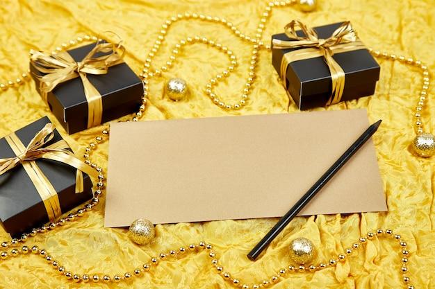 Czarne pudełka na prezenty ze złotą wstążką i pustym arkuszem papieru