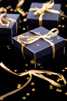 Czarne pudełka ze złotą wstążką na tle blasku