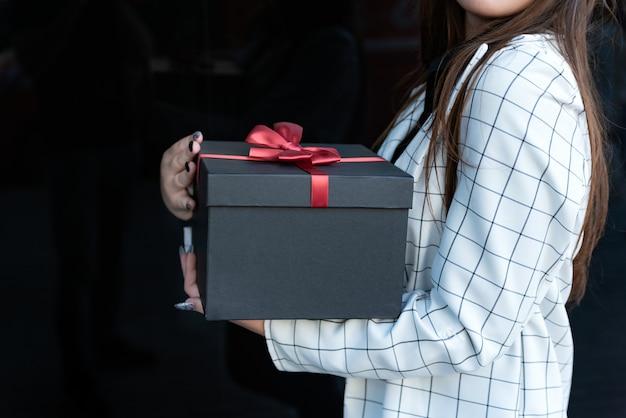Czarne pudełko z czerwoną kokardą w kobiece ręce na czarnym tle. dziewczyna trzyma piękne pudełko w jej ręce. skopiuj miejsce.