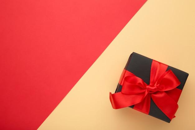 Czarne pudełko z czerwoną wstążką i kokardą na beżowo-czerwonym kolorze.