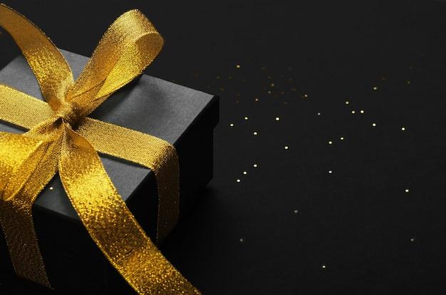 Czarne pudełko z złotą kokardą w tle widoku z góry.