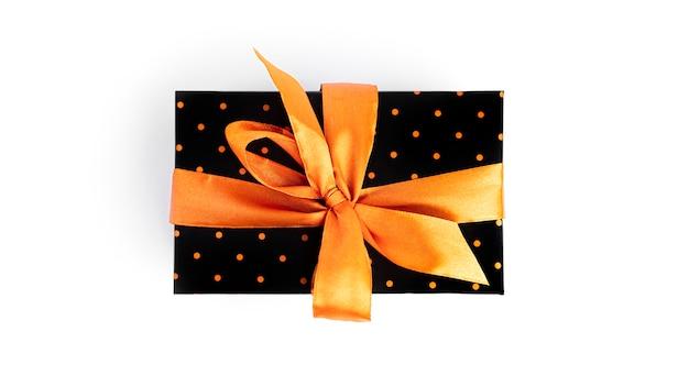 Czarne pudełko ze złotą wstążką na białym tle na białej powierzchni