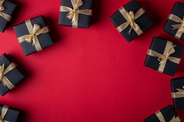 Czarne pudełko ze złotymi wstążkami na czerwonym papierze