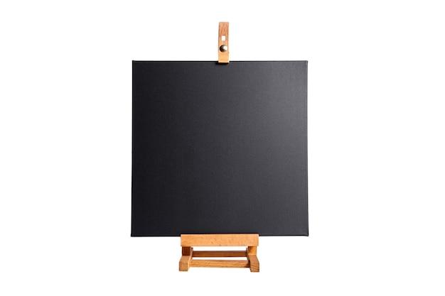 Czarne puste płótno bawełniane i drewniany stół sztalugi, na białym tle. przedni widok