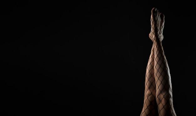 Czarne rajstopy kabaretki na smukłych nogach podniesione na czarnym tle transparentu z miejscem na tekst