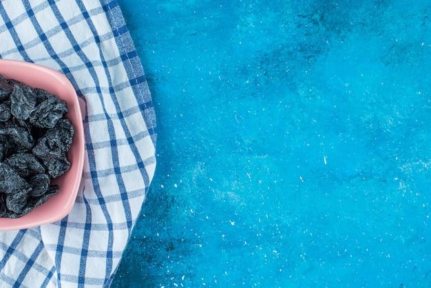 Czarne rodzynki w misce na ściereczce, na niebieskim stole.