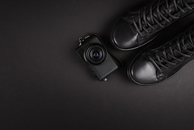 Czarne skórzane buty męskie i czarny aparat na czarnym tle. skopiuj miejsce