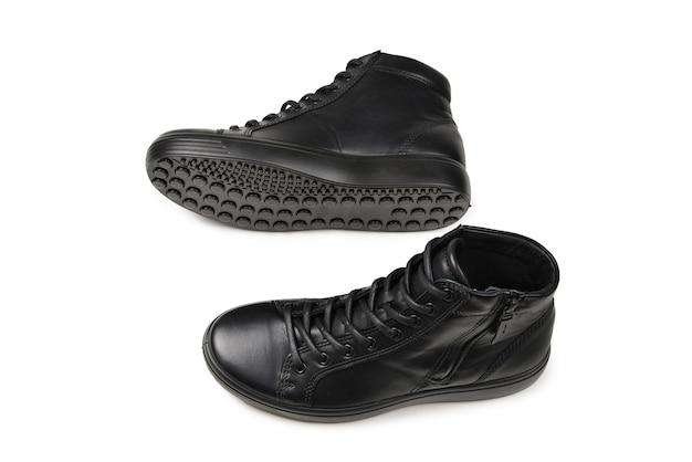 Czarne skórzane buty męskie i czarny aparat na na białym tle. skopiuj miejsce.